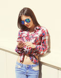 Pretty girl in sunglasses and checkered shirt using the smartphone outdoors Stock Photo