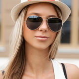 Pretty girl in sunglasses and hat standing at the wall. Europe Royalty Free Stock Images