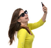 Pretty girl in sunglasses make self portrait selfie with her sma Royalty Free Stock Photos