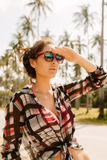 Pretty girl in sunglasses posing to the camera. Close up of a young stylish hipster woman in fashion sunglasses look forward and posing to the camera on tropic Royalty Free Stock Image