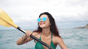 Pretty girl in sunglasses rowing in a kayak stock video