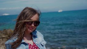 Pretty girl in sunglasses is sitting on the seashore and smiling to camera. Portrait. 4k stock video footage