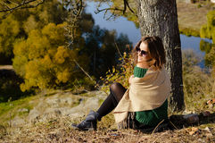 Pretty girl in sunglasses sitting under tree on Royalty Free Stock Photography