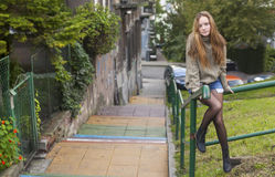 Pretty girl in a sweater sitting on a railing street stairs. Stock Images