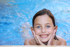 Pretty girl in swimming pool. A pretty girl with blue eyes swimming in a swimming pool Royalty Free Stock Photo