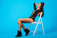 Pretty girl in swimsuit sitting on a chair. Blue background Stock Photography