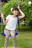 Pretty girl on a swing. In the garden royalty free stock photos