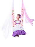 Pretty girl swinging on floral swing Stock Photos
