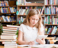 Pretty girl with tablet computer working in library Stock Photography