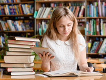 Pretty girl with tablet computer working in library Stock Image