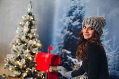 Pretty girl taking envelope from red pree box. stock photography