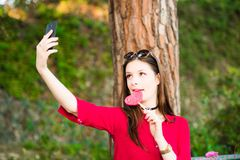 Pretty girl is taking a selfie with a lollipop. Stock Photo