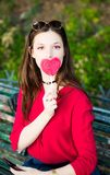 Pretty girl is taking a selfie with a lollipop. Stock Image