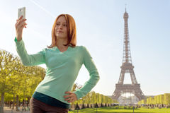 Pretty girl taking a. Selfie in Paris, France on Eiffel Tower background Royalty Free Stock Photography