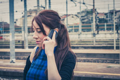 Pretty girl talking on phone along the tracks Royalty Free Stock Photography