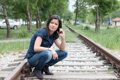 Pretty Girl Talking On Phone Along The Tracks Royalty Free Stock Photos