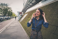 Pretty girl talking on phone in the city streets Stock Photo