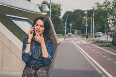 Pretty girl talking on phone in the city streets Royalty Free Stock Images