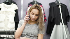 Pretty girl talking on the phone in a clothing store 4K. stock video footage