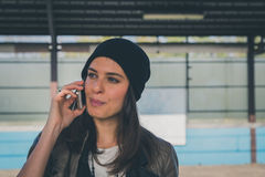 Pretty girl talking on phone in a metro station Royalty Free Stock Photo