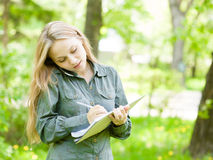 Pretty girl talking on the phone and writes in notebook Royalty Free Stock Photo