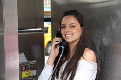 Pretty girl talking by public telephone Stock Image