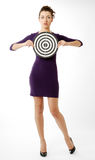 Pretty girl with target. Young woman is holding with both hands target in front of herself, isolated on white. Her elbows are parted. She is wearing short slinky Stock Images