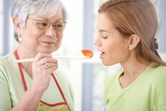 Pretty girl tasting sauce prepared by mother Stock Photo