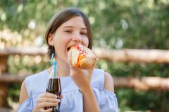 Pretty girl with tasty fast food outdoors. Picnic on the nature. Royalty Free Stock Photography