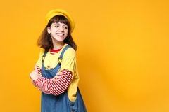 Pretty girl teenager in french beret, denim sundress holding hands folded, looking aside isolated on yellow wall. Background in studio. People sincere emotions stock image