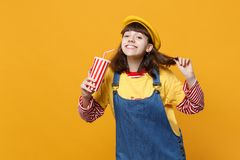Pretty girl teenager in french beret, denim sundress holding plastic cup of cola or soda isolated on yellow wall. Background in studio. People sincere emotions stock photo