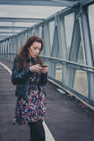 Pretty girl texting on a bridge Stock Images