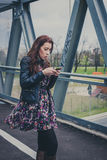 Pretty girl texting on a bridge Royalty Free Stock Photos