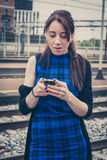 Pretty girl texting on phone along the tracks Royalty Free Stock Images
