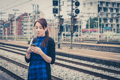 Pretty girl texting on phone along the tracks Stock Image