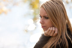 Pretty girl thinking by a river Stock Images