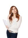 Girl thinking while writing on notepad. Royalty Free Stock Image