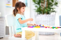 A pretty girl of three years old sits at the table and sculpts figures from colored clay. Sculpting and children`s creativity.  royalty free stock photography