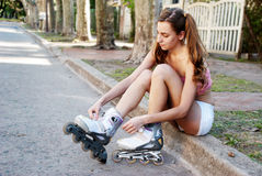 A pretty girl ties the laces on her Rollerblades Royalty Free Stock Images