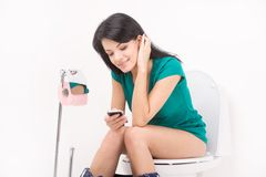 Pretty girl on toilet with cell phone and smiling. Stock Image