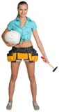 Pretty girl in tool belt holding white helmet and Royalty Free Stock Photos