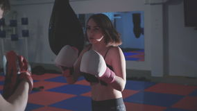 Pretty girl with trainer exercising kickboxing in gym in 4K