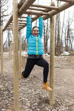Pretty girl training on monkey bars obstacle Stock Photos