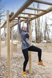 Pretty girl training on monkey bars obstacle Royalty Free Stock Image