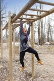 Pretty girl training on monkey bars obstacle Stock Photo