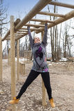 Pretty girl training on monkey bars obstacle Royalty Free Stock Images
