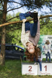 Pretty girl training on a tree. Pretty girl doing exercise upside down on open air Royalty Free Stock Photography