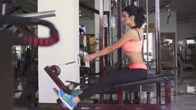 Pretty girl training the triceps with simulator in the modern gym stock video footage
