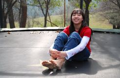 Pretty Girl on Trampoline. Pretty young girl, smiling while sitting on a trampoline Stock Image