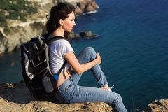 Pretty girl traveler is sitting on rock edge with backpack Royalty Free Stock Photo
